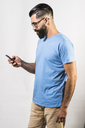 spanish looking: Studio shot of hipster style man touching smartphone on white background