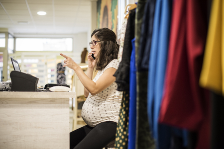 work clothes: Pregnant woman working in clothes store near to computer