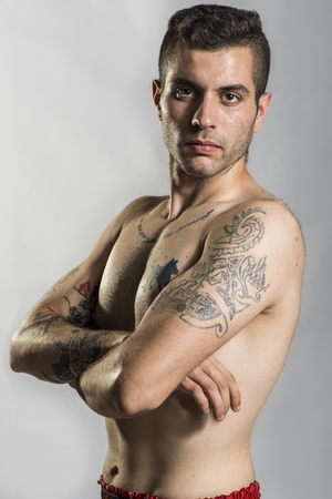 arm tattoo: Young man posing with tattoos in studio shot, like bad boy. Stock Photo
