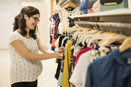 xxxl: Pregnant woman in clothes store looking some clothes to buy