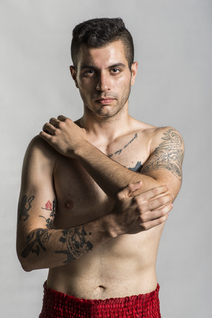 man in jail: Young man posing with tattoos in studio shot, like bad boy. Stock Photo