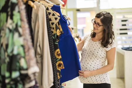 tienda de ropa: Mujer embarazada en la tienda de ropa buscando algo de ropa para comprar Foto de archivo