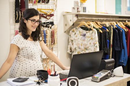 Zwangere vrouw die in kleding winkel in de buurt van de computer Stockfoto
