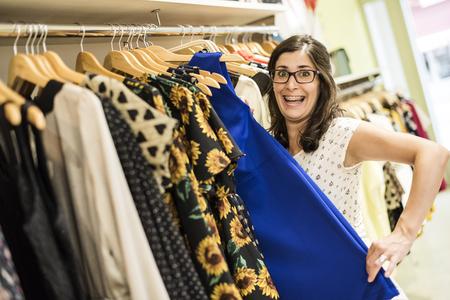 loco: Mujer embarazada en la tienda de ropa buscando algo de ropa para comprar Foto de archivo