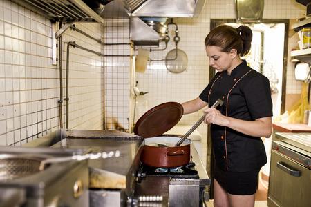 sexy young girls: Молодая женщина работает в старой кухне, улыбаясь и приготовления пищи