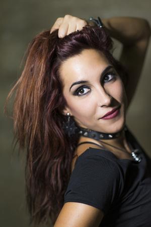 �spiked: Mujer joven con estilo de metal g�tico y pesado y posando collar de pinchos en el fondo de la pared sucia