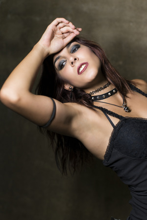 heavy metal: Young woman with gothic and heavy metal style and spiked collar posing on dirty wall background Stock Photo