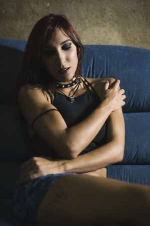 20s: Sexy 20s gothic woman relaxing in sofa Stock Photo