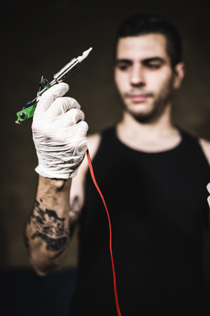 bad hygiene: Defocused man posing with tattoo machine Stock Photo