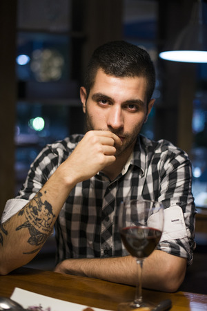 tatouage sexy: Seductive man in restaurant ooking at camera drinking wine