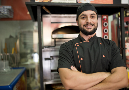 near: Turkish man posing near to oven