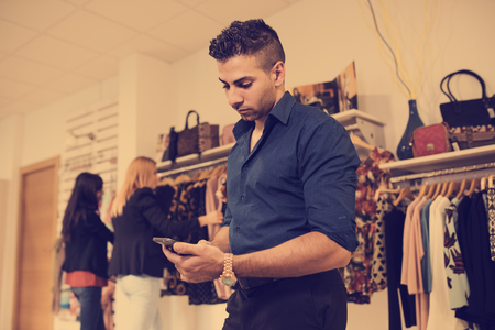distraction: Boring man looking phone while his girlfriends shopping