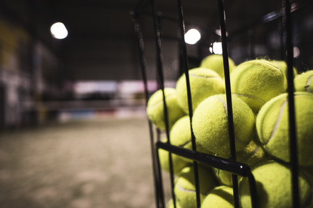 Paddle tennis basket in court with balls. Stock Photo