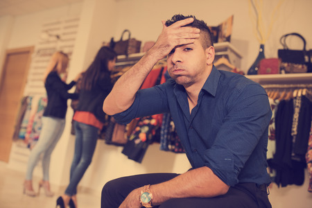 cliche: Boring man waiting his girlfriends end shopping session Stock Photo