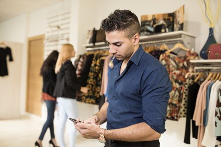 cliche: Boring man looking phone while his girlfriends shopping