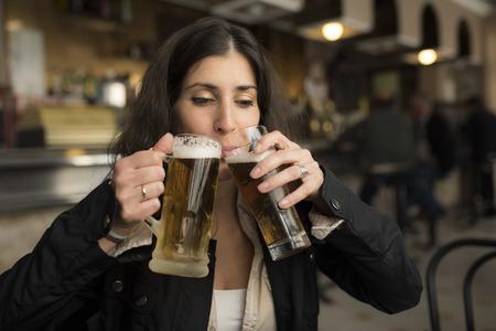 jarra de cerveza: Mujer feliz bebiendo cerveza en la barra con el ambiente y la iluminación natural