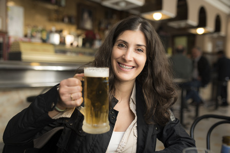 ambient: Happy woman drinking beer in bar with ambient and natural lightning