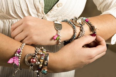 adjusting: Woman adjusting bracelets closeup studio image Stock Photo