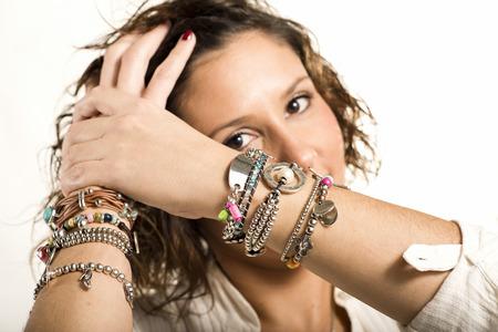 forearm: Happy woman showing bracelets isolated on white background Stock Photo