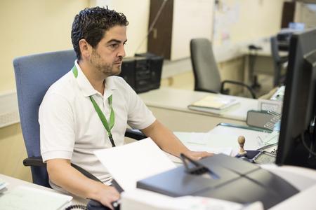 jornada de trabajo: Hombre de mediana edad que trabajan en su oficina usando la computadora.