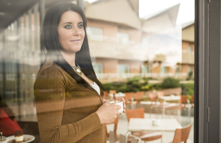 dark haired woman: Dark haired woman with cup of coffee standing behind cafes window while looking away
