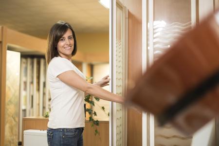 cabine de douche: Portrait de femme souriante adulte regardant la caméra tout en choisissant une cabine de douche en magasin
