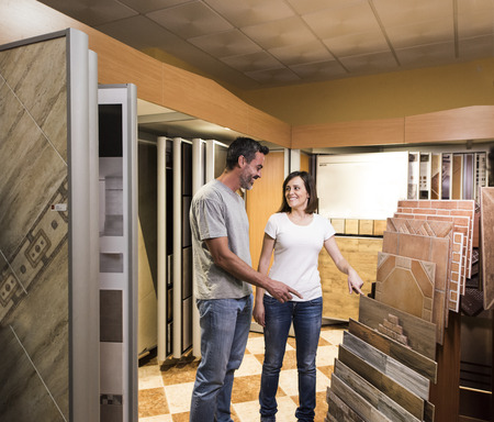 Happy couple choosing tile for bathroom in store