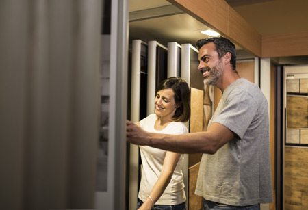 bathroom tile: Adult happy couple looking at bathroom tile in furniture store Stock Photo