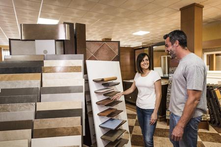 bathroom tile: Happy couple of adults choosing ceramic tile for bathroom