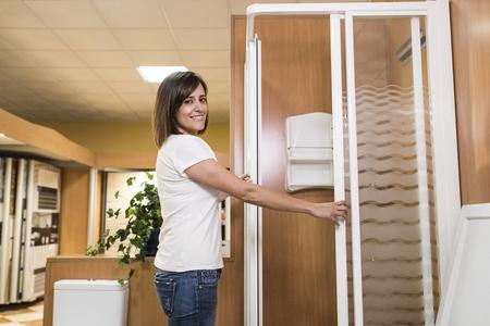 cabine de douche: Belle femme souriante à la recherche d'une cabine de douche dans la salle de magasin de meubles