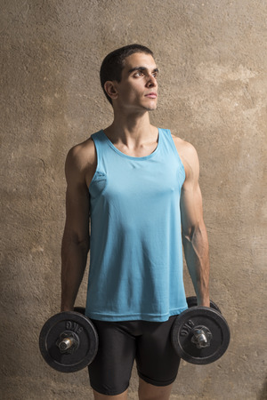 abdominal wall: Young man lifting weights in studio shot with wall background Stock Photo