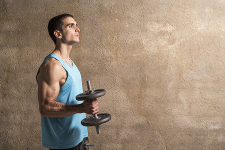 Young man lifting weights in studio shot with wall background Stock Photo
