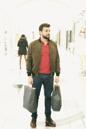 Bearded 30-35 years man shopping with bags in mall center outdoors with casual clothes. photo