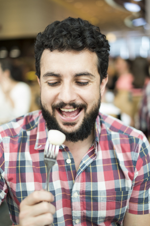 Man eating fruit in restaurant. Close up hipster 35 years old man portrait photo