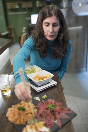Woman eating sushi and sashimi in restaurant