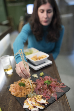 Woman eating sushi and sashimi in restaurant photo