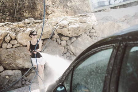 Woman cleaning black car with pressurized water photo