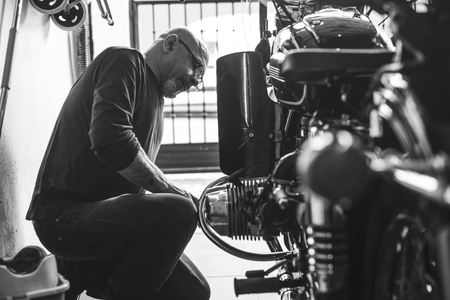 Monochrome images of senior man cleaning his sidecar bike Фото со стока