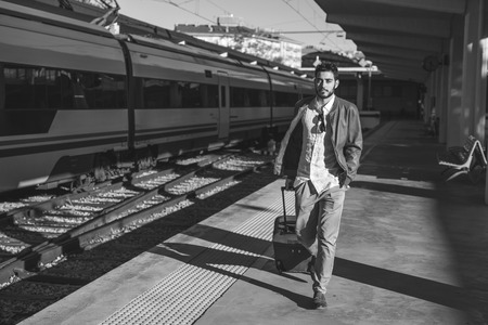 Young man in train station waiting for travel Stock Photo