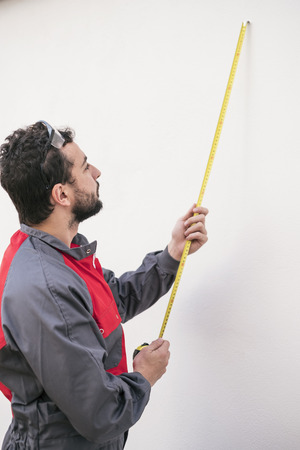 Worker man measuring size of home improvement and reforms Stock Photo