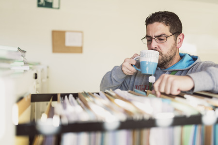 Offise worker drinking tea while looking for some files at work Stock Photo