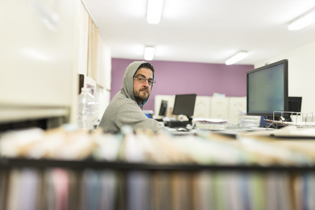40 years old man looking computer and working with sweatshirt and hood in office