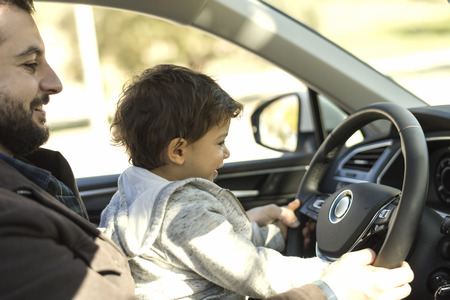 Father playing teaching baby to drive car while waiting inside for something