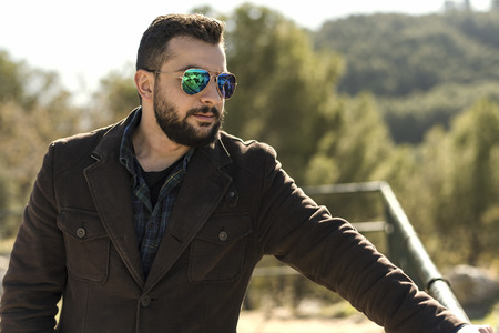 Outdoors man portrait with beard and sunglasses
