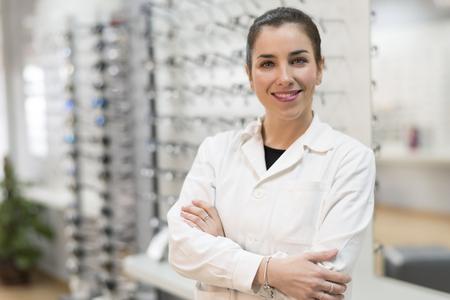 Posing optometrist woman in eyeglasses store smiling looking at camera