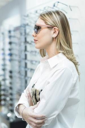 Woman trying on sunglasses in optical store