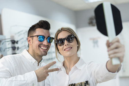 Couple trying on sunglasses in optical store and looking mirror