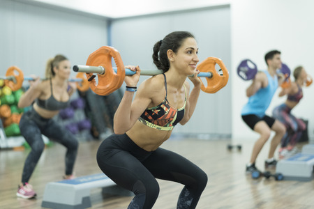 People training body pump and isometric exercises at gym Фото со стока - 93155153