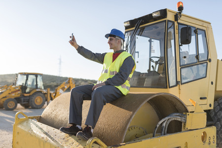 Man with smartphone on heavy vehicle. Work distractions