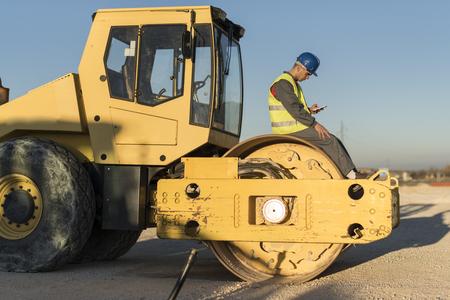 건설 노동자가 굴삭기 타이어를 수정합니다. 스톡 콘텐츠 - 94686020
